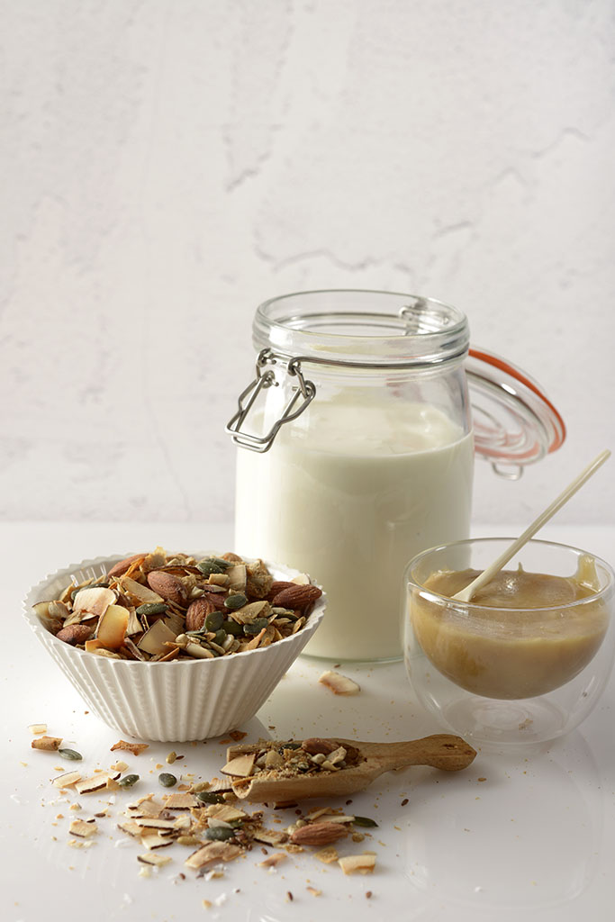 Jar of Instant Pot® Coconut Yoghurt with coconut muesli and coconut blossom sugar on kitchen counter