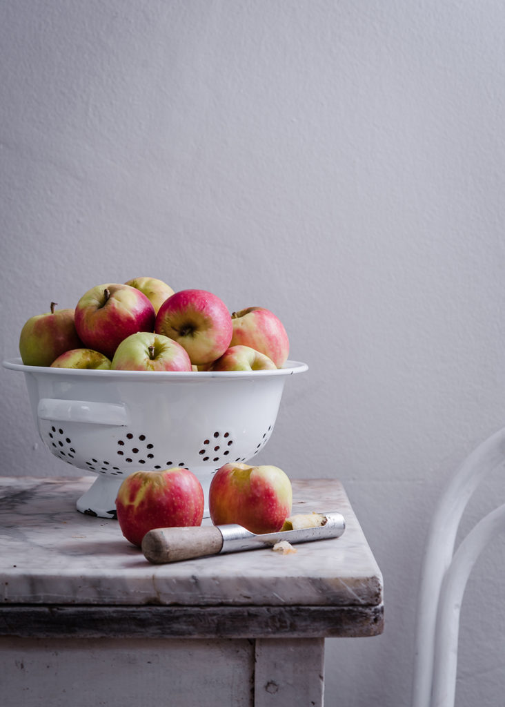 Pink lady apples on marble counter in white enamel colander