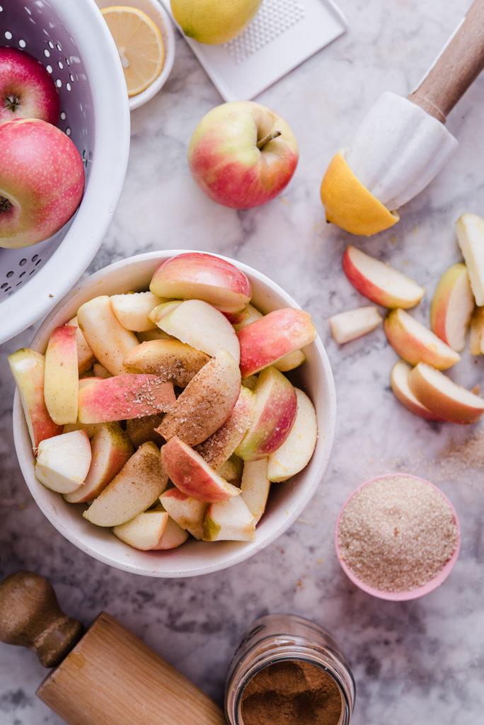 pink apples and cinnamon sugar on marble table