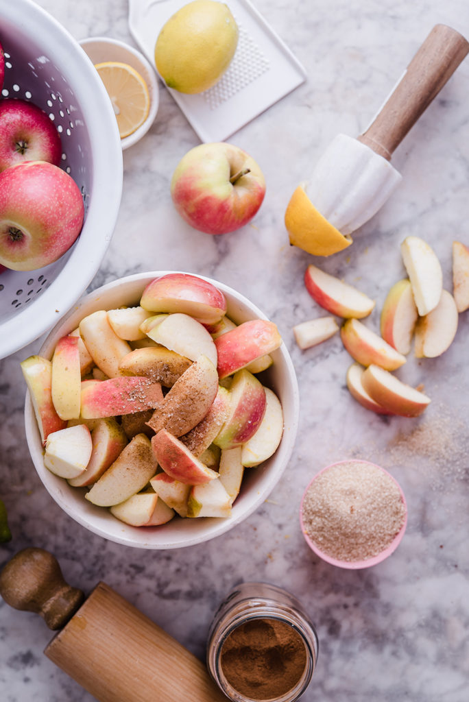 apples on marble with cinnamon and lemon