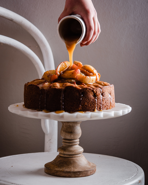 pouring salted caramel sauce on apple cake